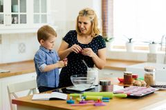 Mother and child preparing cookies in kitchen. Beautiful child and mother baking in kitchen with love stock photo