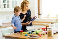 Mother and child preparing cookies. In kitchen royalty free stock photography