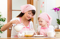 Mother and child preparing cookies together at kitchen Royalty Free Stock Image