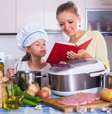 Mother and child preparing meat Royalty Free Stock Photography