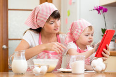 Mother and child preparing pastry looking at cookbook stock photography