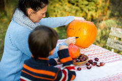 Mother and child preparing pumpkin for Halloween Royalty Free Stock Photography