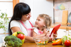Mother and child preparing vegetables together at kitchen and lo. Mother and child girl preparing vegetables together at kitchen and looking at tablet for royalty free stock image