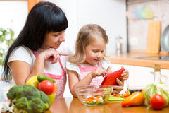 Mother and child preparing vegetables together at kitchen and lo. Mother and kid preparing vegetables together at kitchen and looking at tablet for receipe stock image