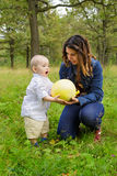 Mother and child with pumpkin. Mother and child holding a big mellow yellow pumpkin Royalty Free Stock Images