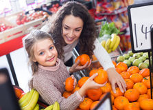 Mother and child purchasing mandarins Stock Image