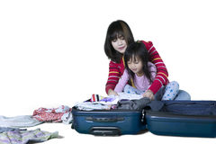 Mother and child put clothes in a suitcase Royalty Free Stock Images