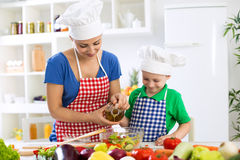 Mother and child putting olive oil to vegetables lettuce Royalty Free Stock Image