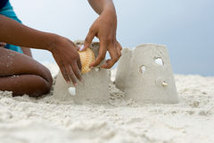 Mother and child putting a shell on a sandcastle Stock Photography