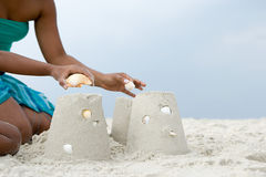 Mother and child putting shells on sandcastles Royalty Free Stock Photos