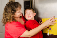 Mother and child putting up boy's art Stock Images