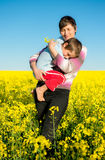 Mother and child on a rapeseed field Stock Photography