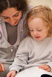 Mother and child reading a book. Mother and daughter reading a book together, sitting on a couch at their home Royalty Free Stock Image