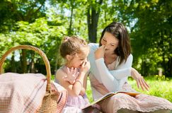 Mother and child - reading book. Mother with child are playing while reading book and imitating elephant Stock Image