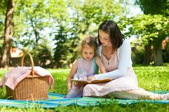 Mother and child - reading book. Mother and child reading book on picnic in park Royalty Free Stock Photos