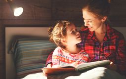 Mother and child reading book in bed before going to sleep Royalty Free Stock Images
