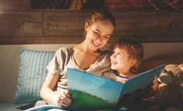 Mother and child reading book in bed before going to sleep Royalty Free Stock Photo