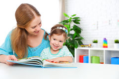 Mother and child reading  book at home Stock Photos