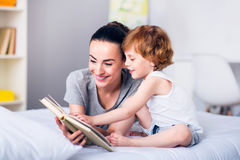 Mother and child reading a book Stock Photos