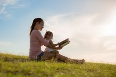 Mother and daughter spending time together reading a book, while sitting at the park stock photography