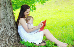 Mother and child reading book together under tree in summer. Park Royalty Free Stock Photo
