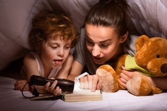 Mother and child reading book under blanket. Bedtime story. Young modern mother reading a tale to her son using a flashlight in a hut of blankets Royalty Free Stock Images