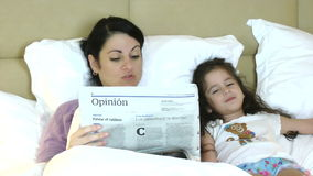 Mother and child reading newspaper in bed having fun stock video footage