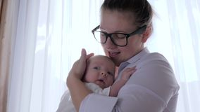 Mother-child relationship, young mum comforts infant into arms in room in natural light near window. With white curtains stock video footage