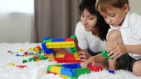 Mother and child resting lying on the bed. happy family playing with meccano color blocks.