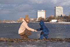 Mother and child on a river bank Royalty Free Stock Photo