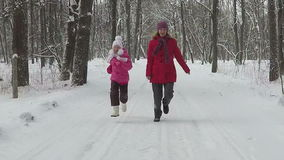 Mother with child run in park at winter day. Slowmotion stock video