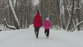 Mother with child run in park at winter day. Slowmotion stock footage