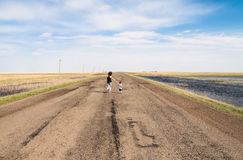 Mother and child running on empty road Royalty Free Stock Images