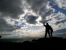 Mother and Child by the Sea. Silhouette of mother and child looking up at the opninous sky at the Puget Sound coast in Western Washington state, USA Stock Images
