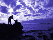 Mother And Child By The Sea. Silhouette of mother and child looking up at the ominous sky at the puget sound coast in western washington state, usa stock photography