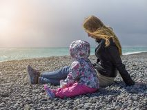 Mother with child on sea coast looking on the sunset Royalty Free Stock Images