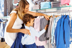 Mother with child searches clothes while  shopping Royalty Free Stock Photo