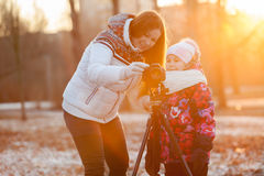 Mother and child set up the camera on tripod in rays of setting sun Royalty Free Stock Photo
