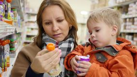 A mother with a child in the shop choosing baby food. Food. a mother with a child in the shop choosing baby food stock video