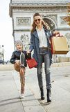Mother and child shopper near Arc de Triomphe going forwar. Stylish autumn in Paris. Full length portrait of happy trendy mother and child with shopping bags Stock Images