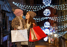 Mother and child with shopping bags among Christmas lights Royalty Free Stock Photography