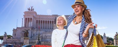 Mother and child with shopping bags looking into distance. Roman Holiday. happy modern mother and child travellers in the front of Palazzo Venezia in Rome, Italy Stock Photography