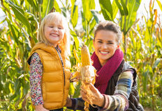 Mother and child showing corn while in cornfield Stock Photos
