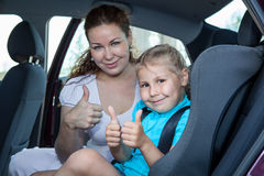 Mother and child showing thumb up gesture in car Stock Image