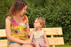 Mother and child sit on bench Stock Images