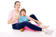 Mother with a child sit and eat apples Royalty Free Stock Images