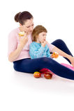 Mother with a child sit and eat apples Royalty Free Stock Photo