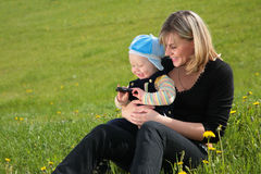 Mother with child sit on grass Stock Photos