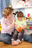 Mother with child sit in playroom Stock Image