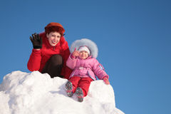 Mother with child sit on snow hill royalty free stock photos